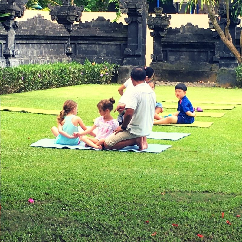 two girls practicing yoga at a kids club in bali