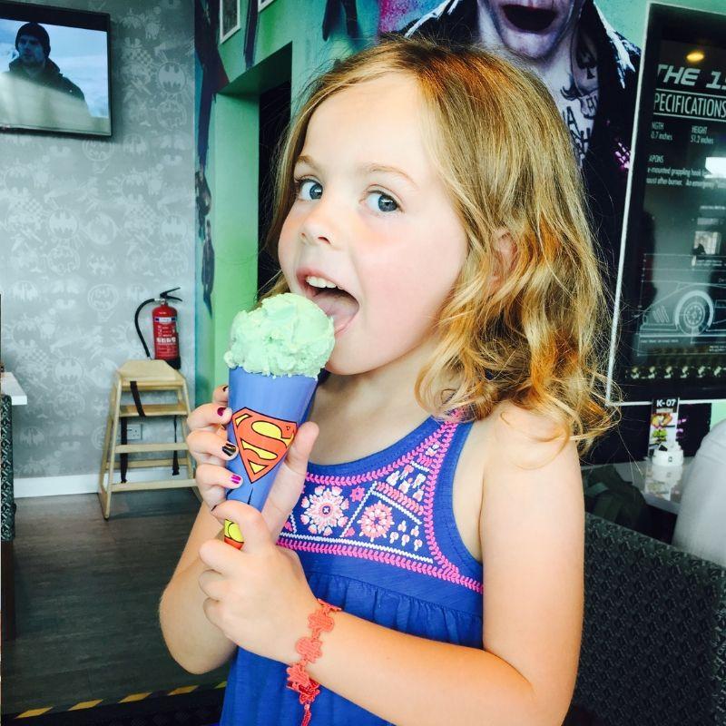 young girl eating green ice cream