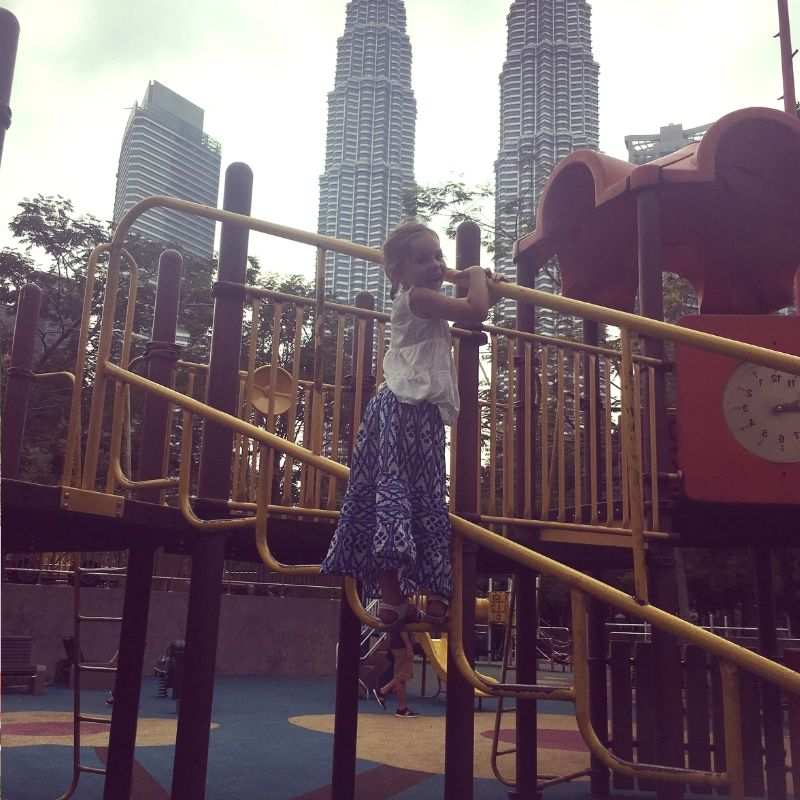 girl playing on play equipment at clock park in kuala lumpur