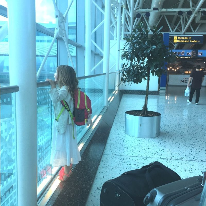 girl in long white dress looking out an airport window