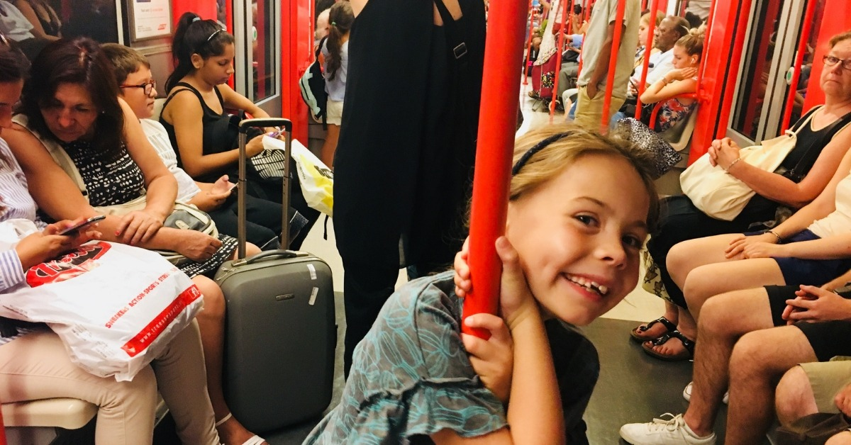 girl on train in italy holding on to a red pole