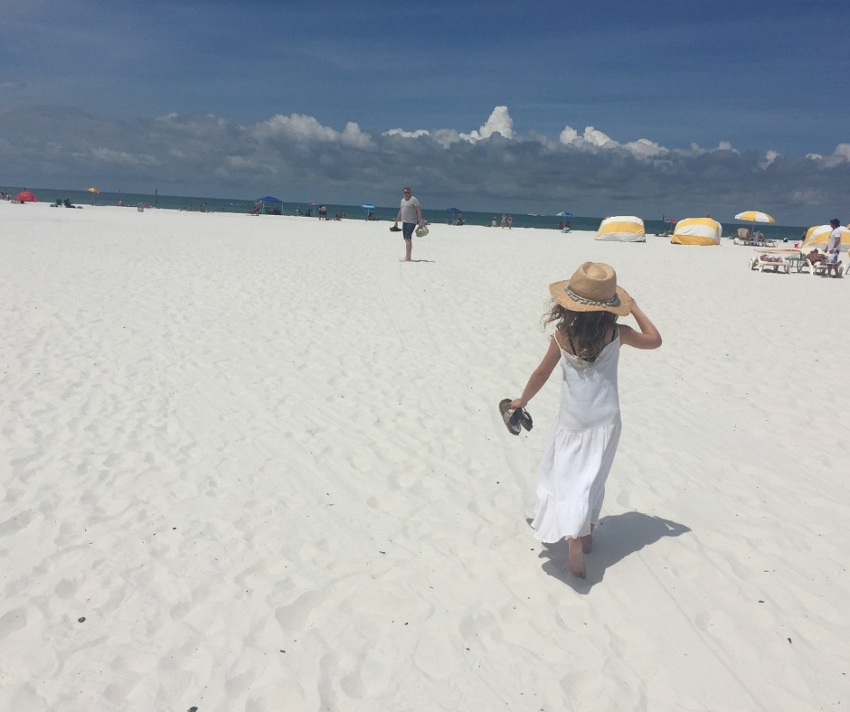 father and daughter on a white beach, she is wearing a long white dress and straw hat