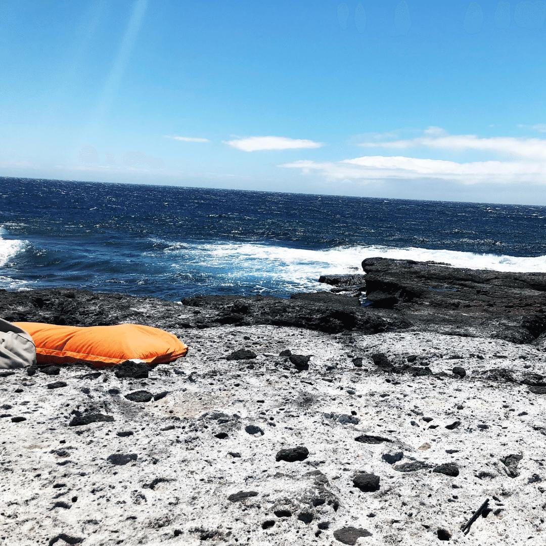 bright orange beanbag on a black rock beach at the roca negra sunset club