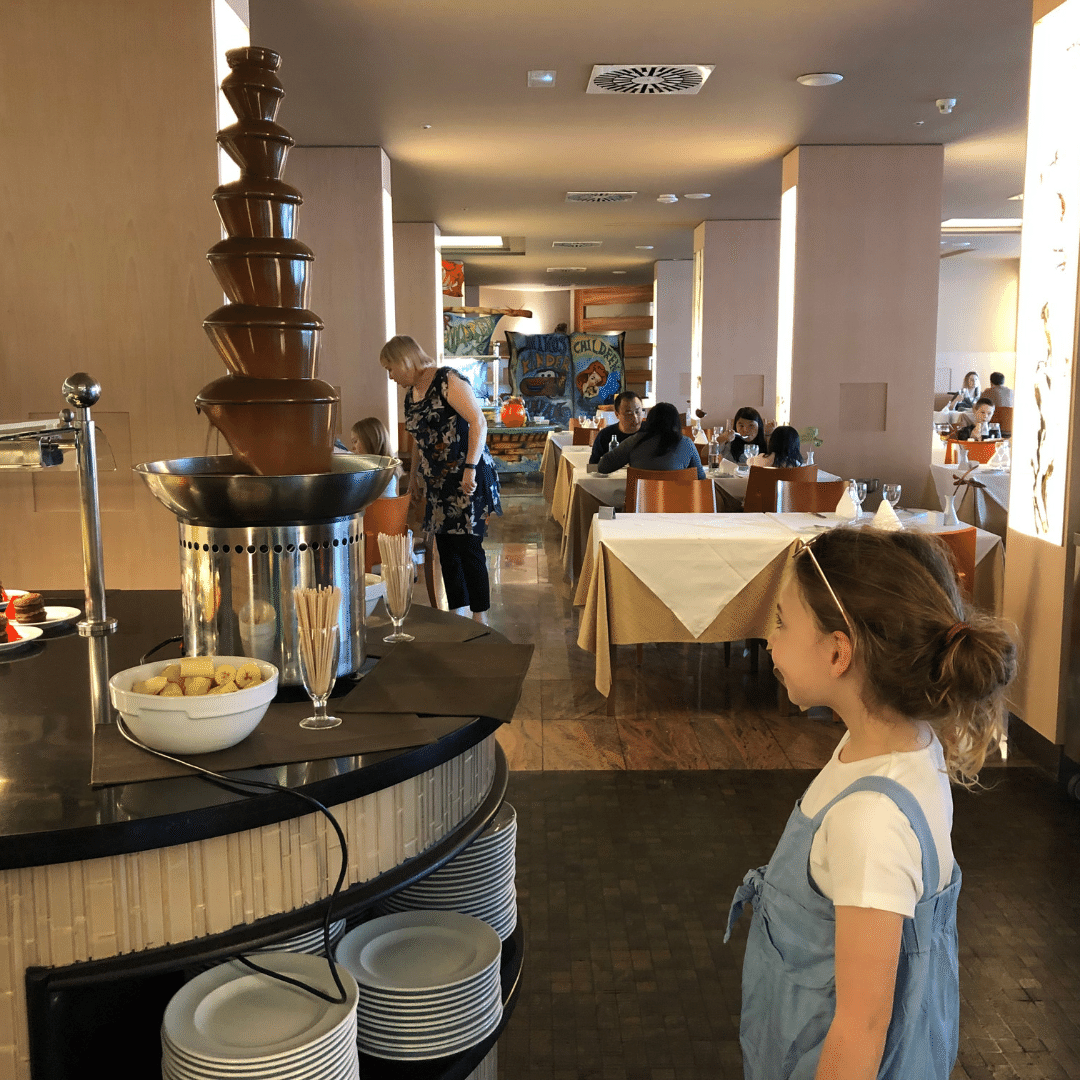 piper quinn staring at a chocolate fountain in the buffet restaurant at the hotel in tenerife
