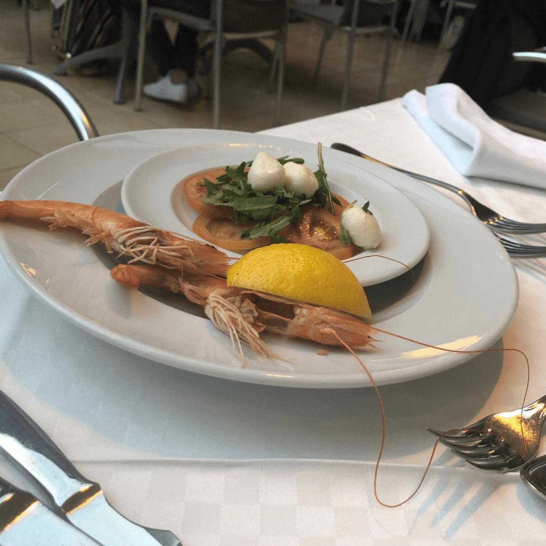 plate of fresh prawns, lemon and a tomato salad