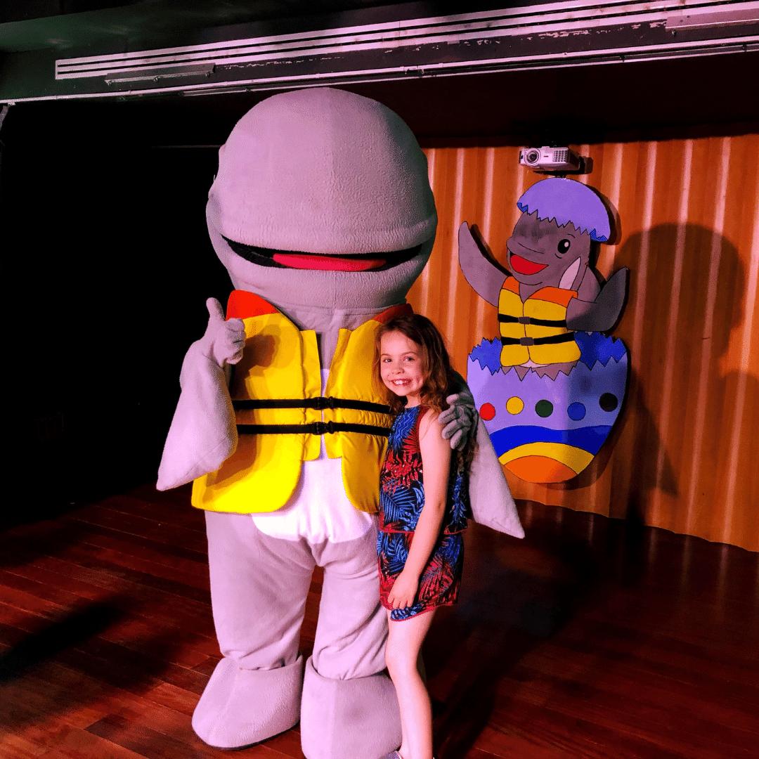 piper quinn having a hug with roni the whale mascot at the roca nivaria