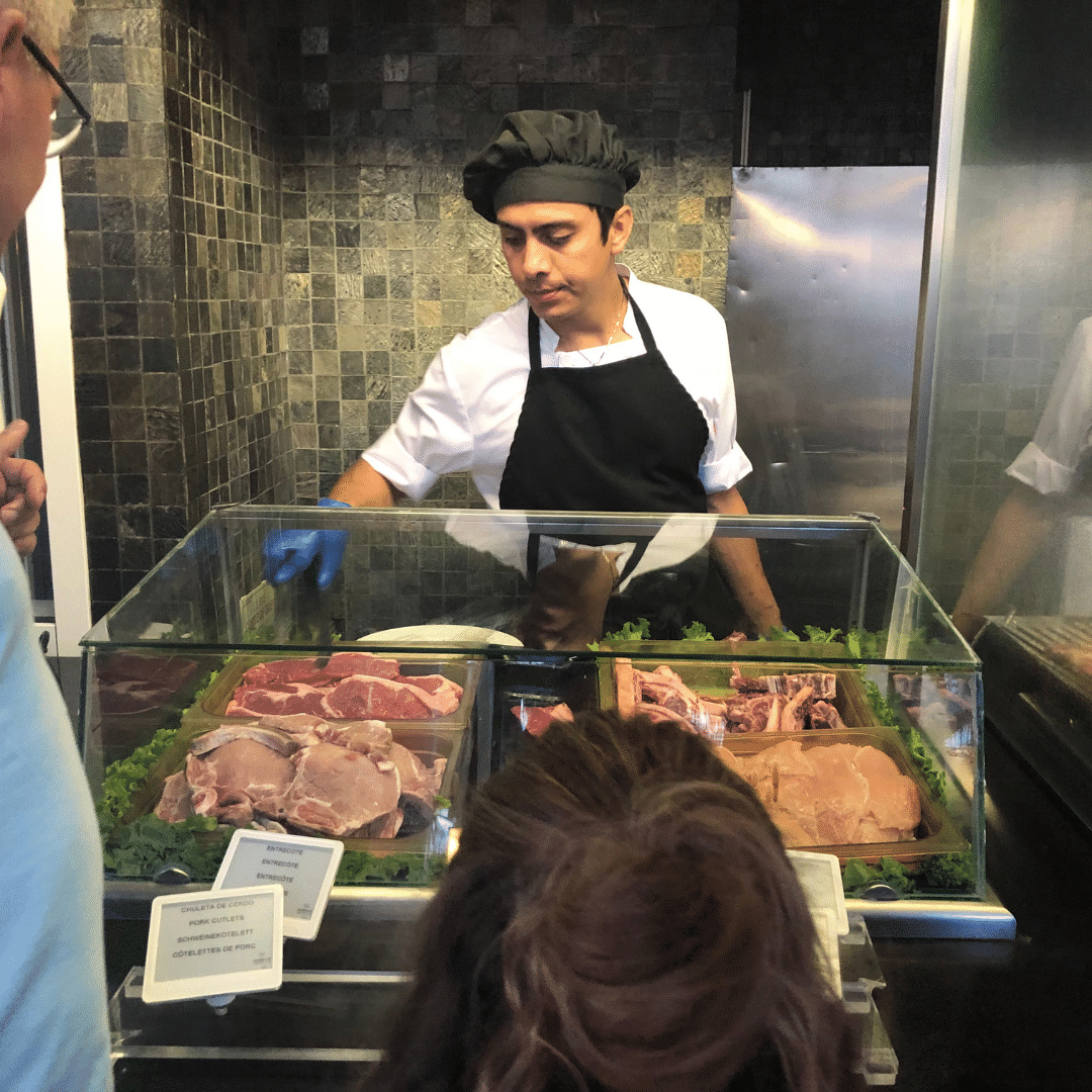chef serving at an out door grill with huge chops, steaks and seafood