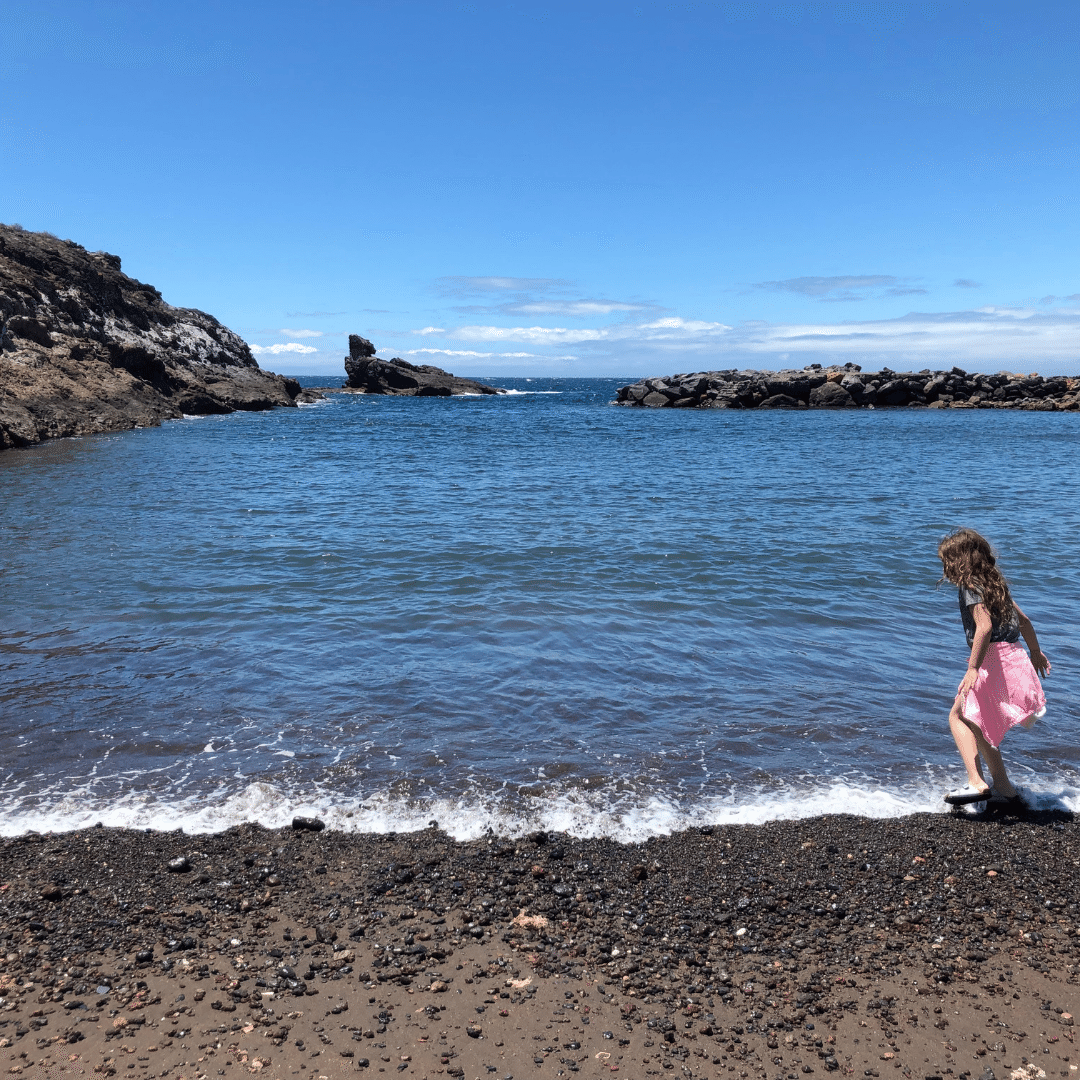 piper quinn skimming stones on a black beach in playa paraiso