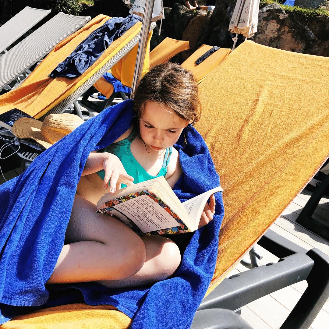 eight year old girl reading a book on a sun lounger wearing a turquoise bikini
