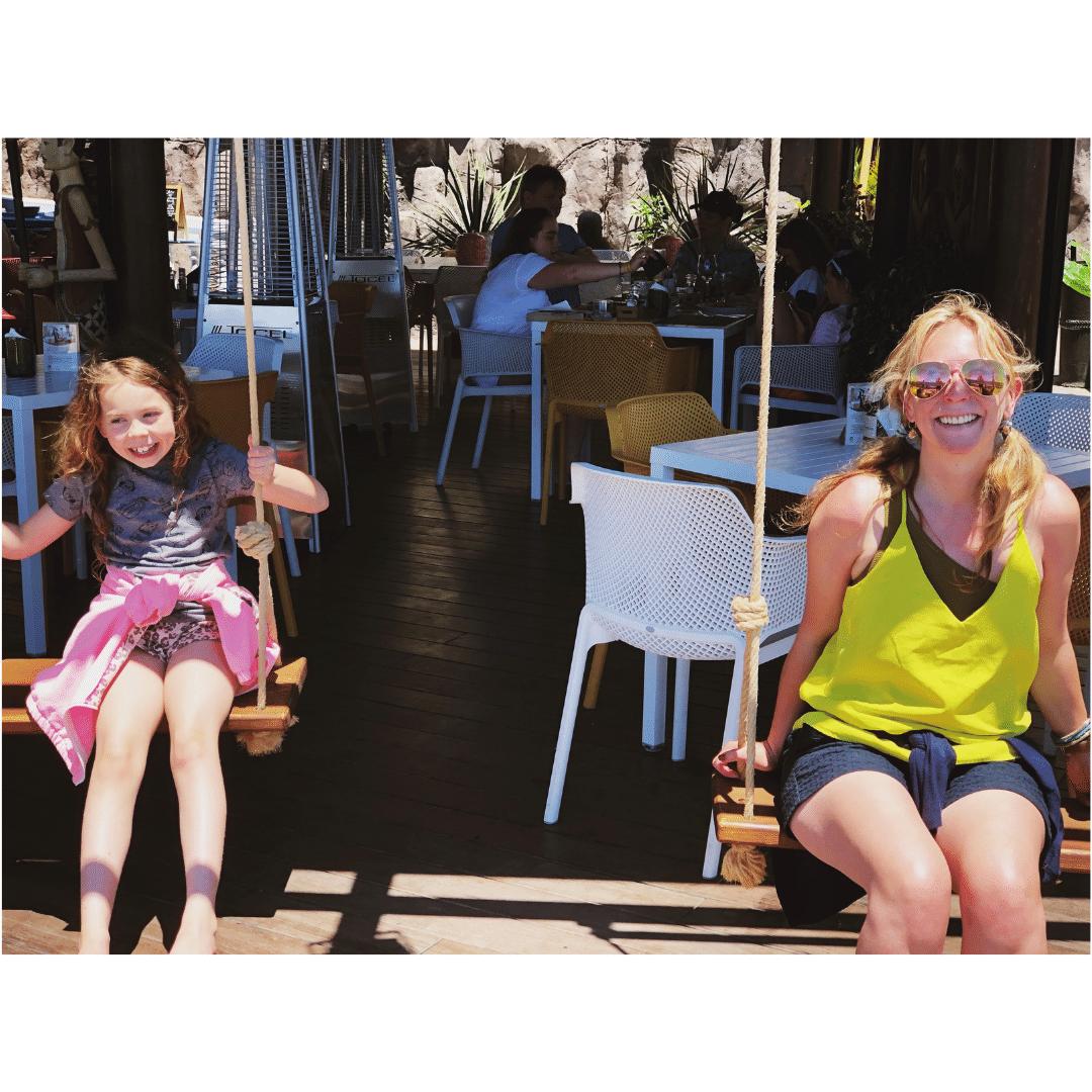 piper quinn and karen quinn sat on wooden swings outside the roca negra beach club