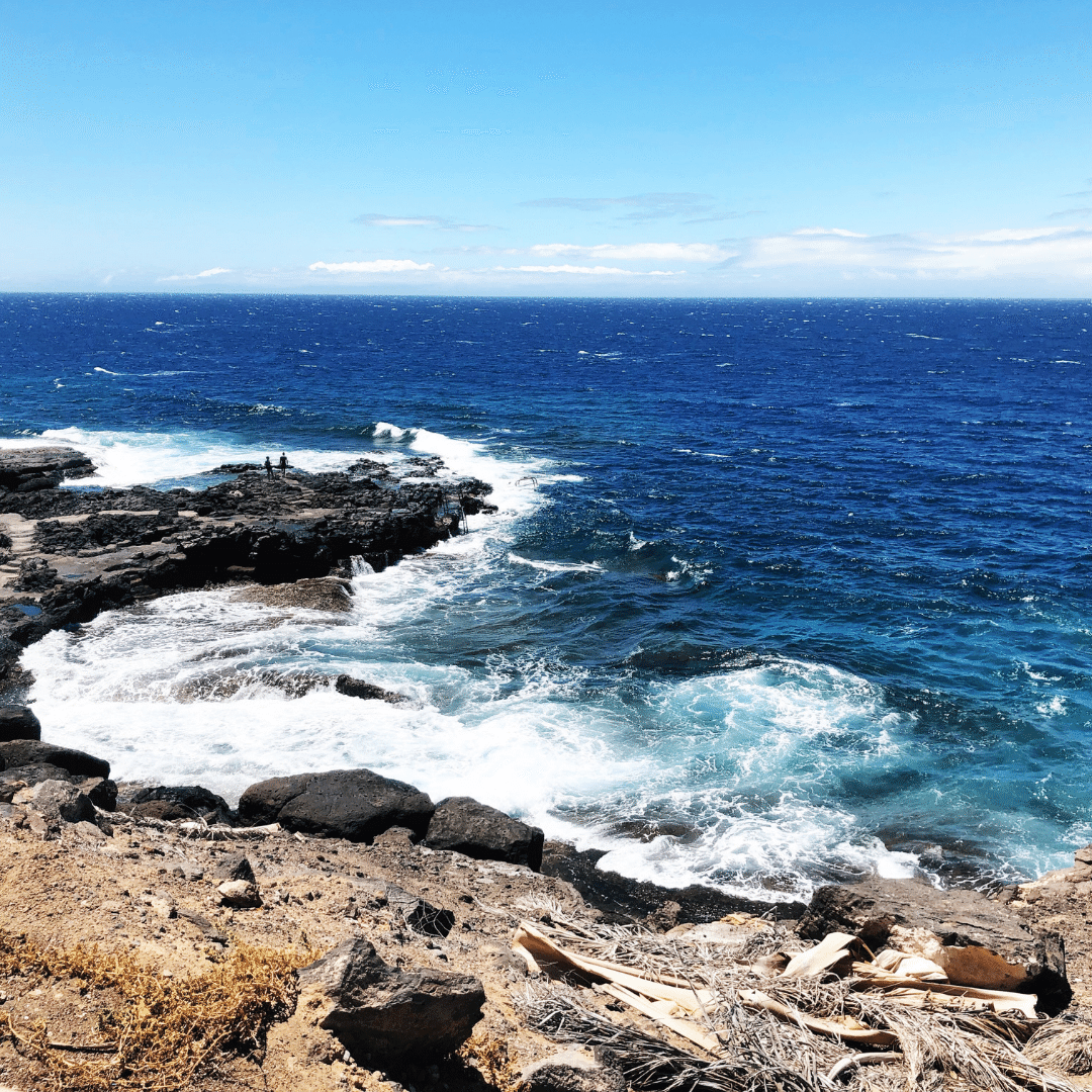 black rock beach in tenerife, the sky is bright blue and there are white waves crashing against the rocks