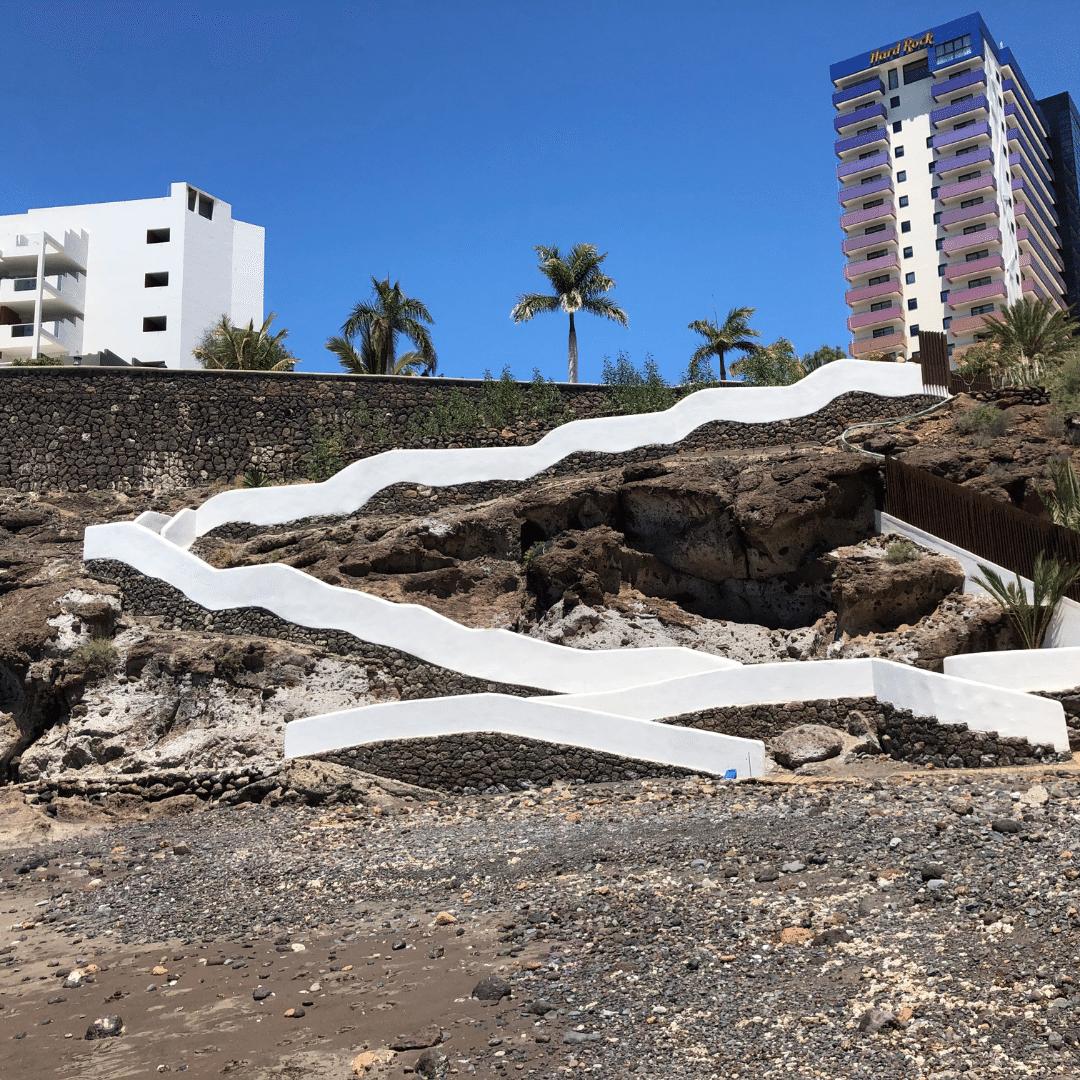 winding white steps down a black cliffside to a black sand beach