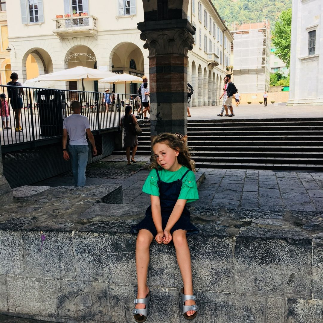 eight year old girl looking tired on the steps in Como