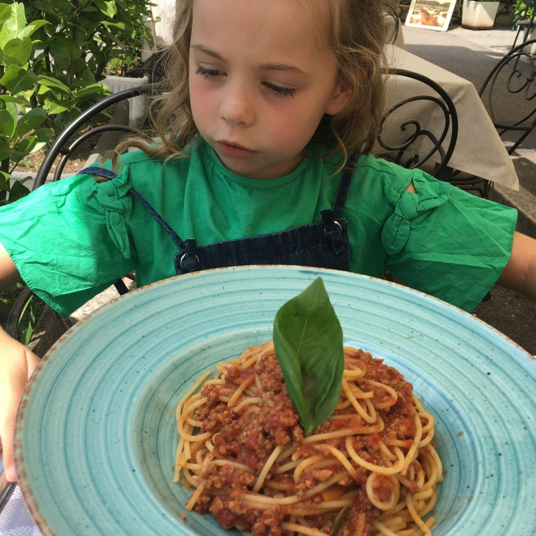 young girl in front of huge bowl of spaghetti bolognaise