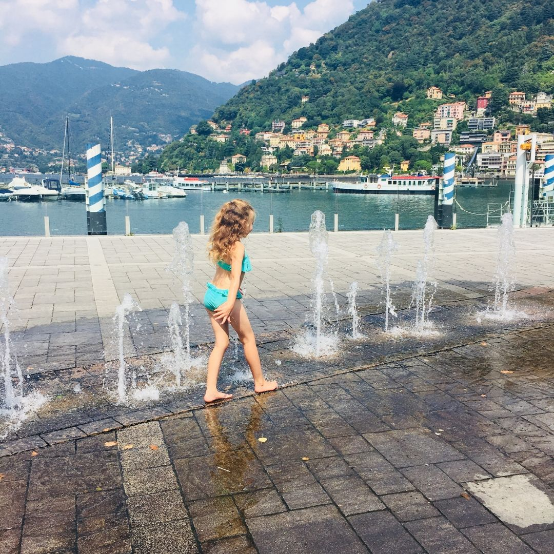girl playing in splash fountains in como, italy