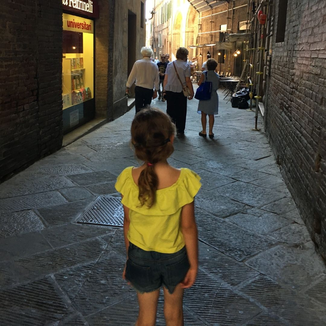 young girl exploring the alleyways in siena, tuscany
