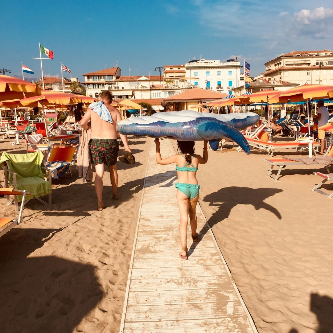 7 year old girl holding an inflatable on her head on the beach in via reggio