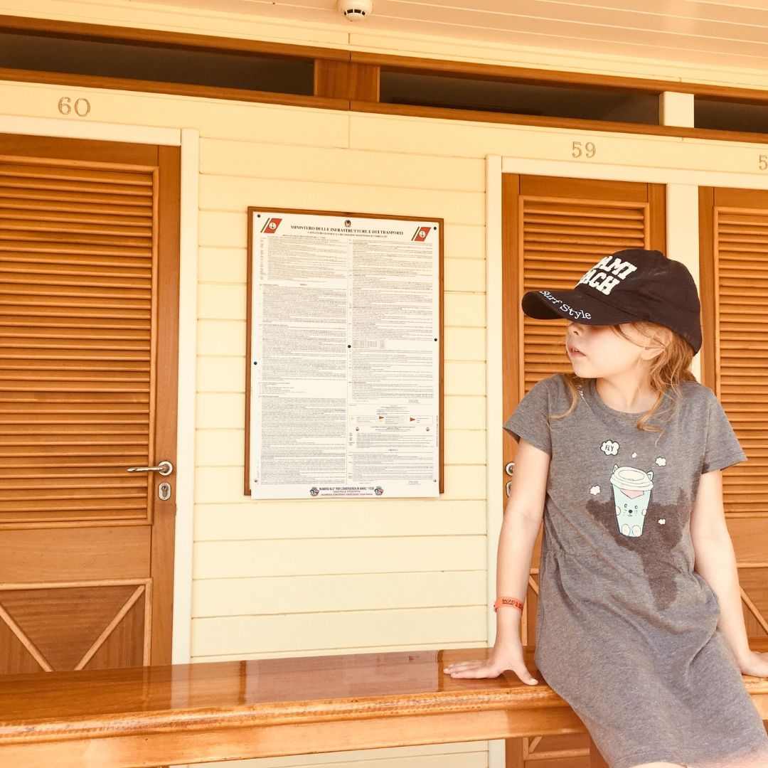young piper quinn at a beach club in a cap and casual dress