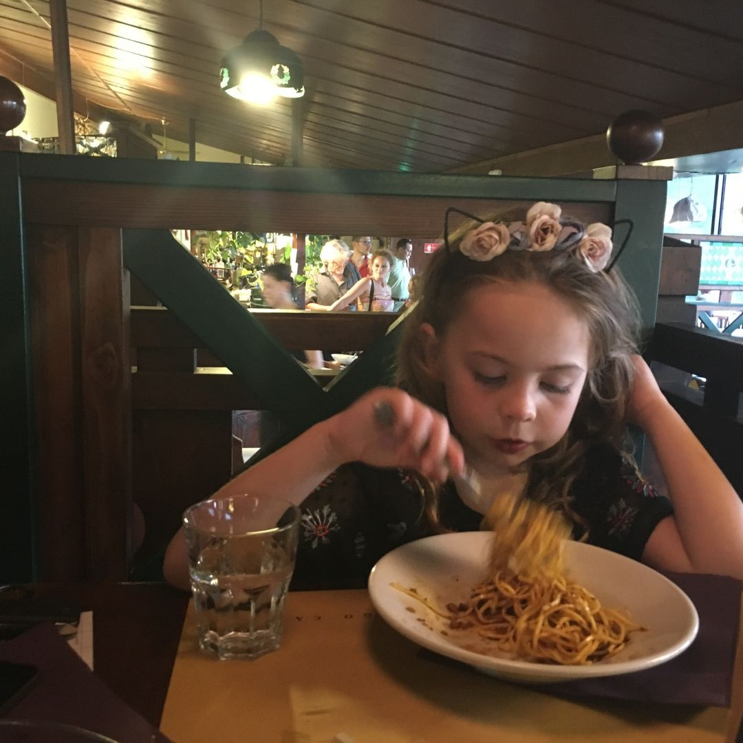young girl enjoying a bowl of pasta in a family restaurant in Tuscany