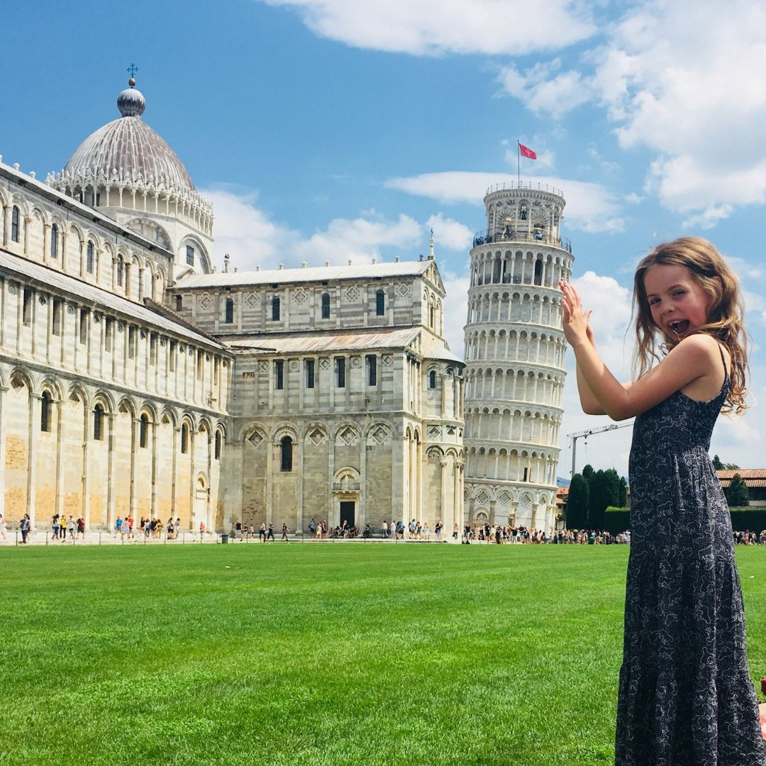 7 year old girl doing the optical illusion trick with the leaning tower of pisa