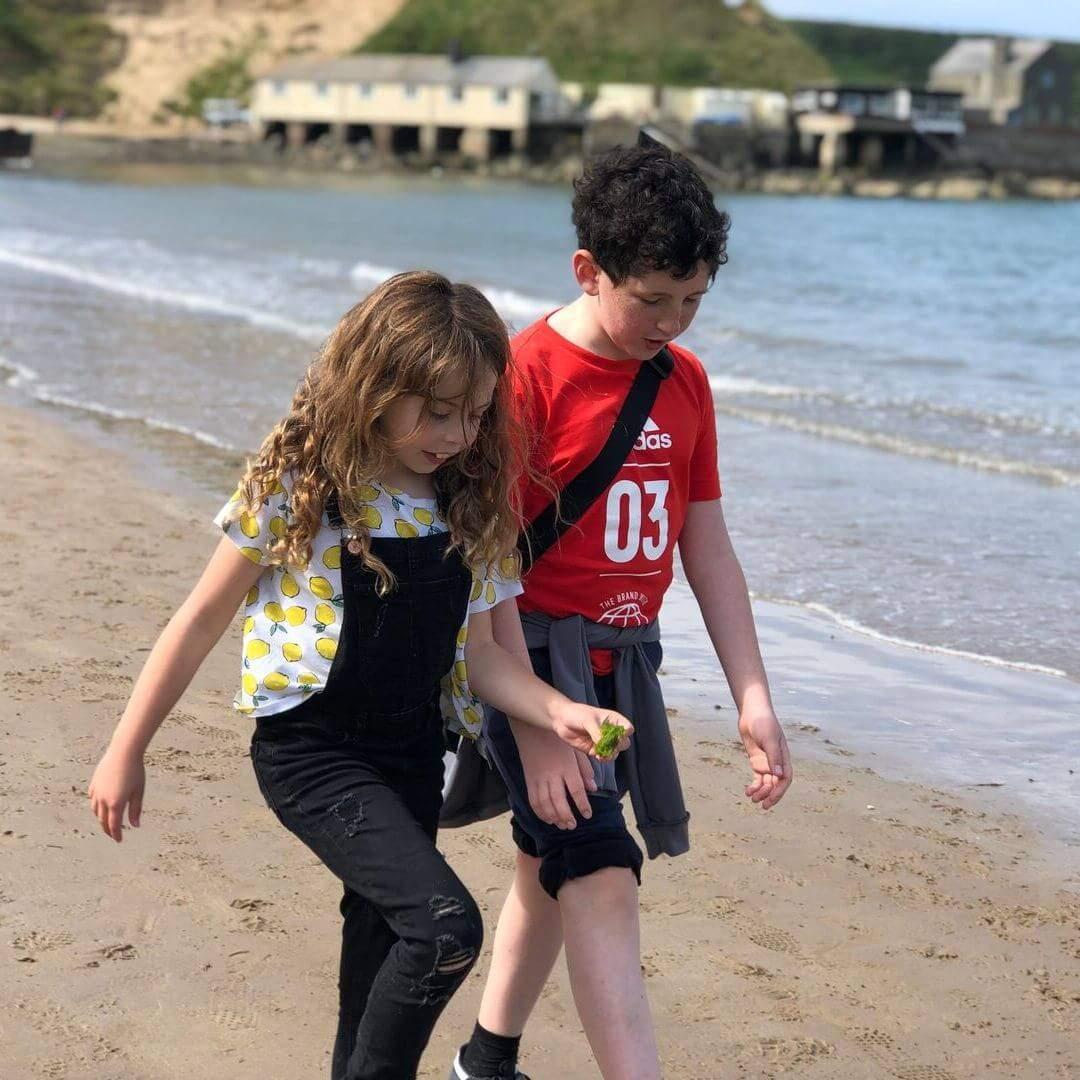 young girl and boy walking along a beach in north wales
