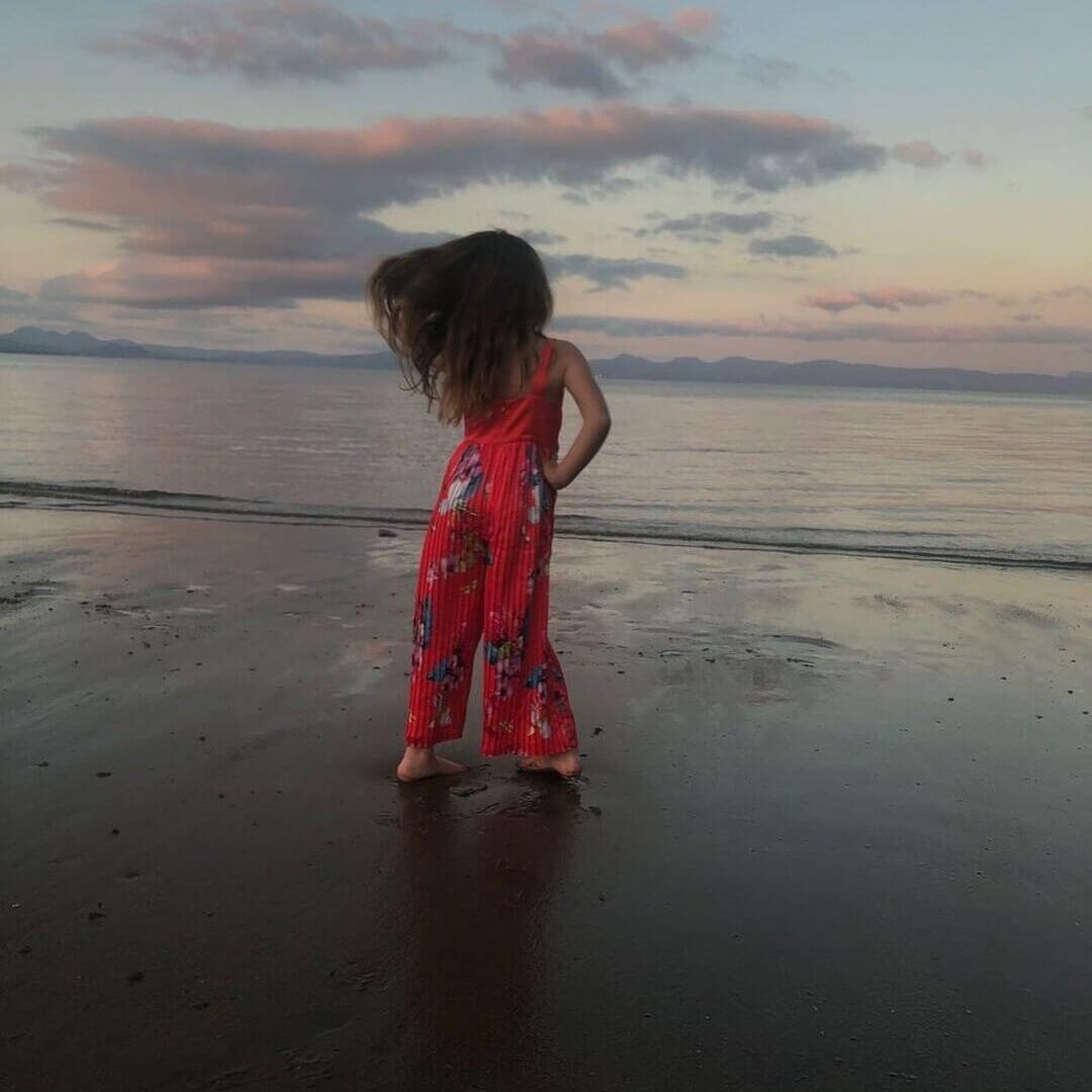 young girl with wind in her hair at sunset at llanbedrog beach