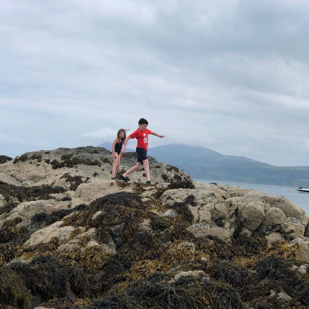 kids climbing on rocks at a beach in North Wales