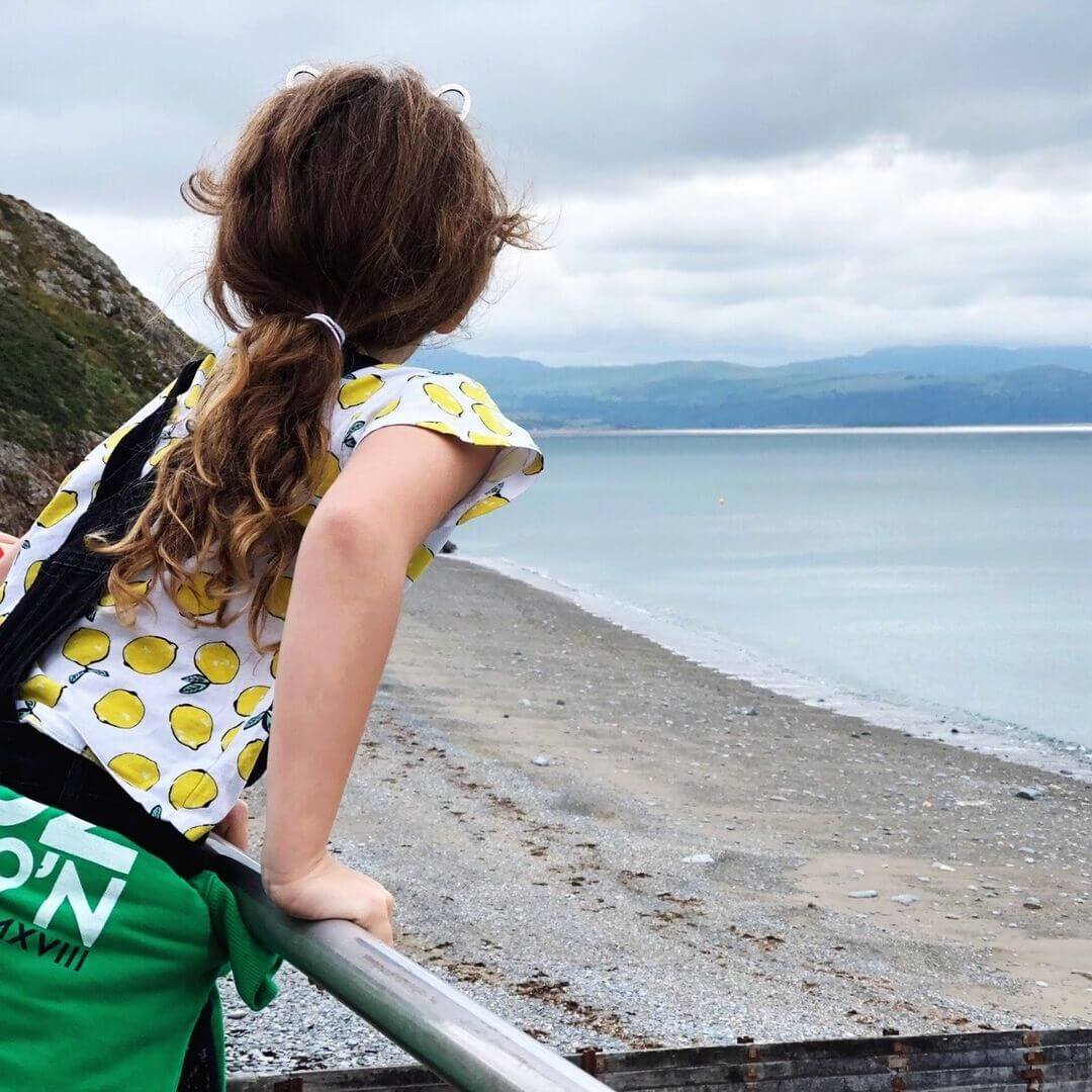 girl looking out to sea at Criccieth beach