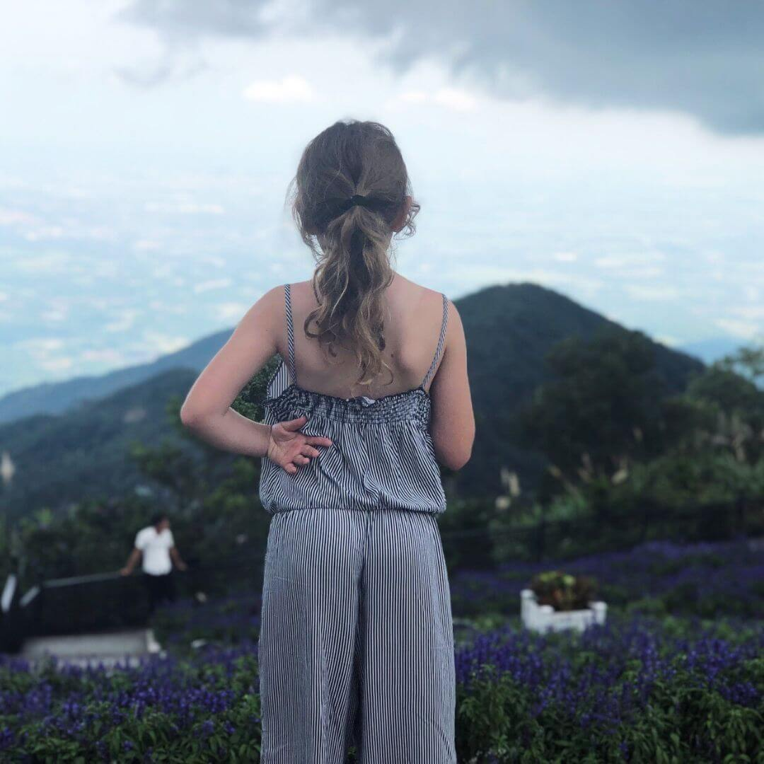 Girl In A Stripy Playsuit Looking Across Mountains From High
