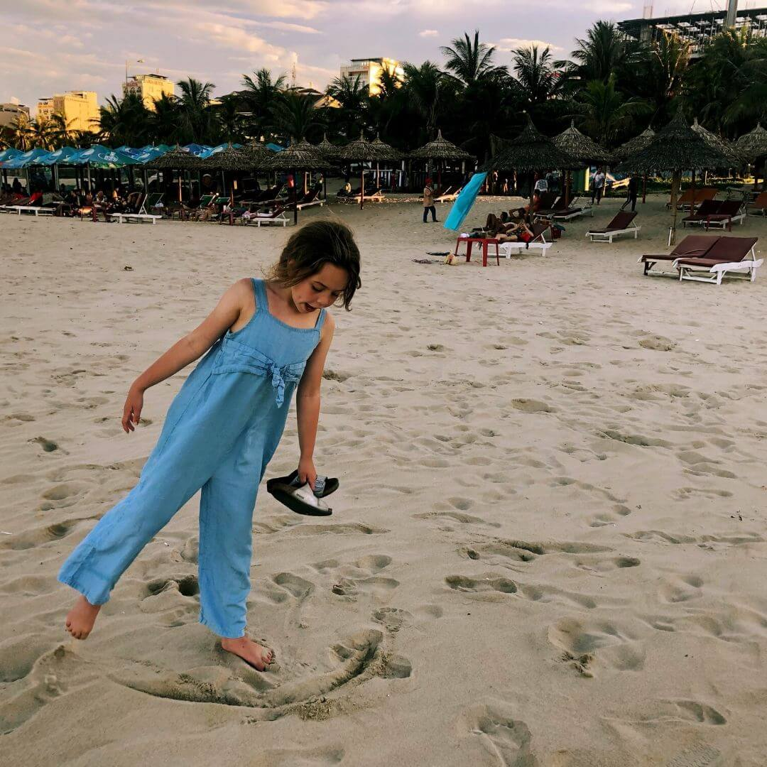 9 year old girl playing in the sand on the beach