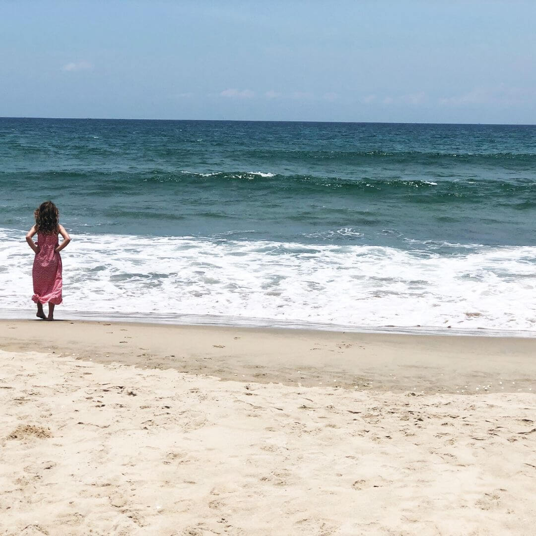 young girl looking out to sea on a white sandy beach