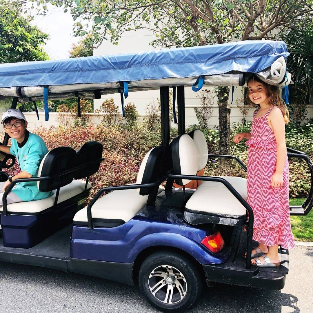 piper quinn standing on the back of a golf buggy