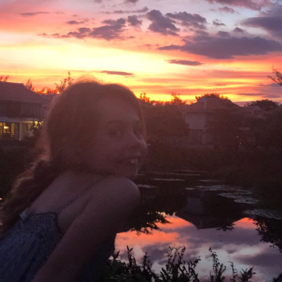 piper quinn smiling in front of a sunset sky in vietnam