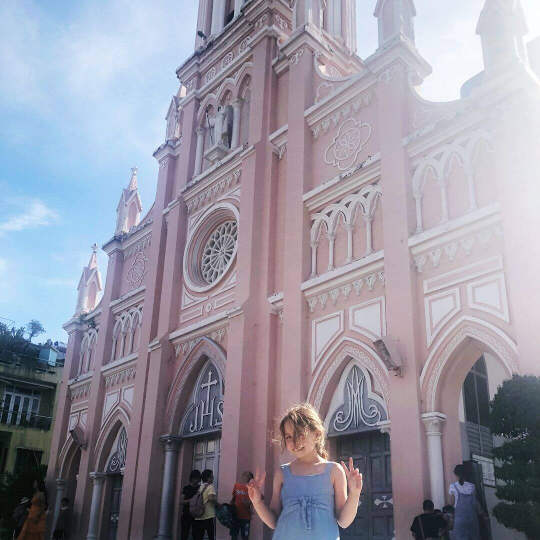 Piper Quinn Smiling Outside The Pink Cathedral In Da Nang. The Sky Is Blue And The Walls Of The Church Are Pale Pink