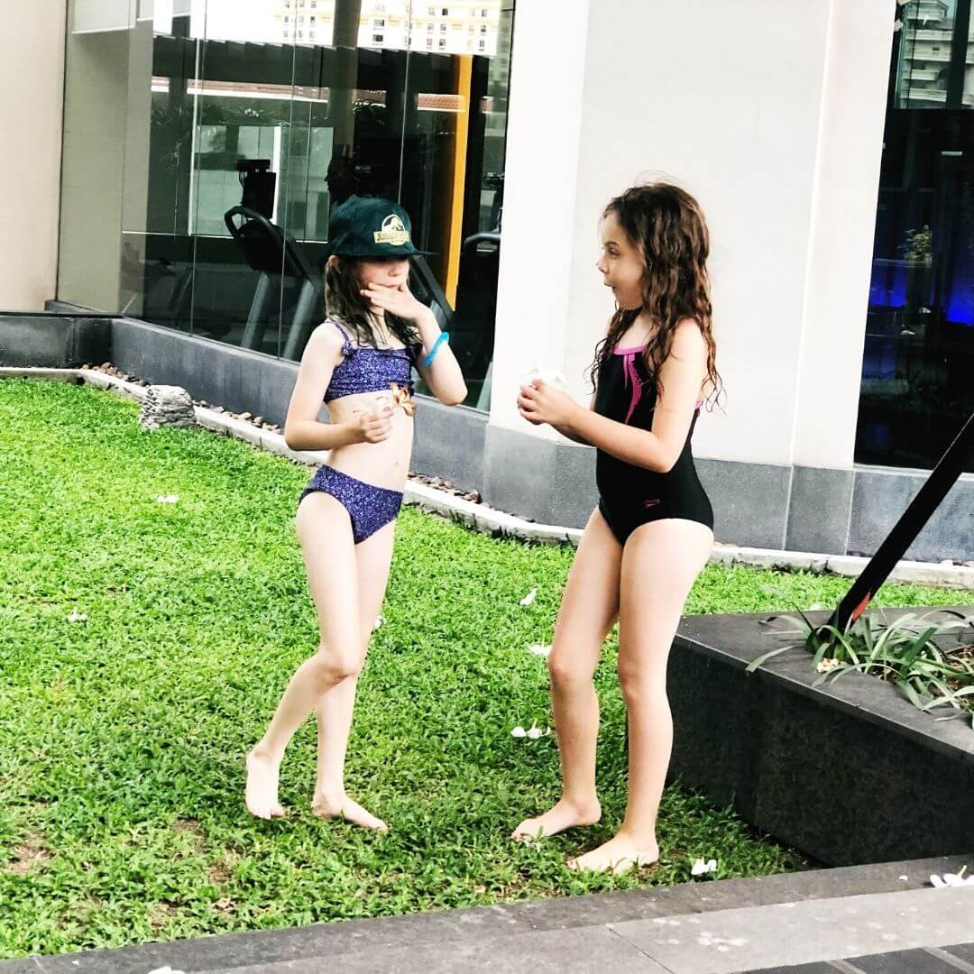 two 9 year old girls in swimsuits playing at a bangkok hotel