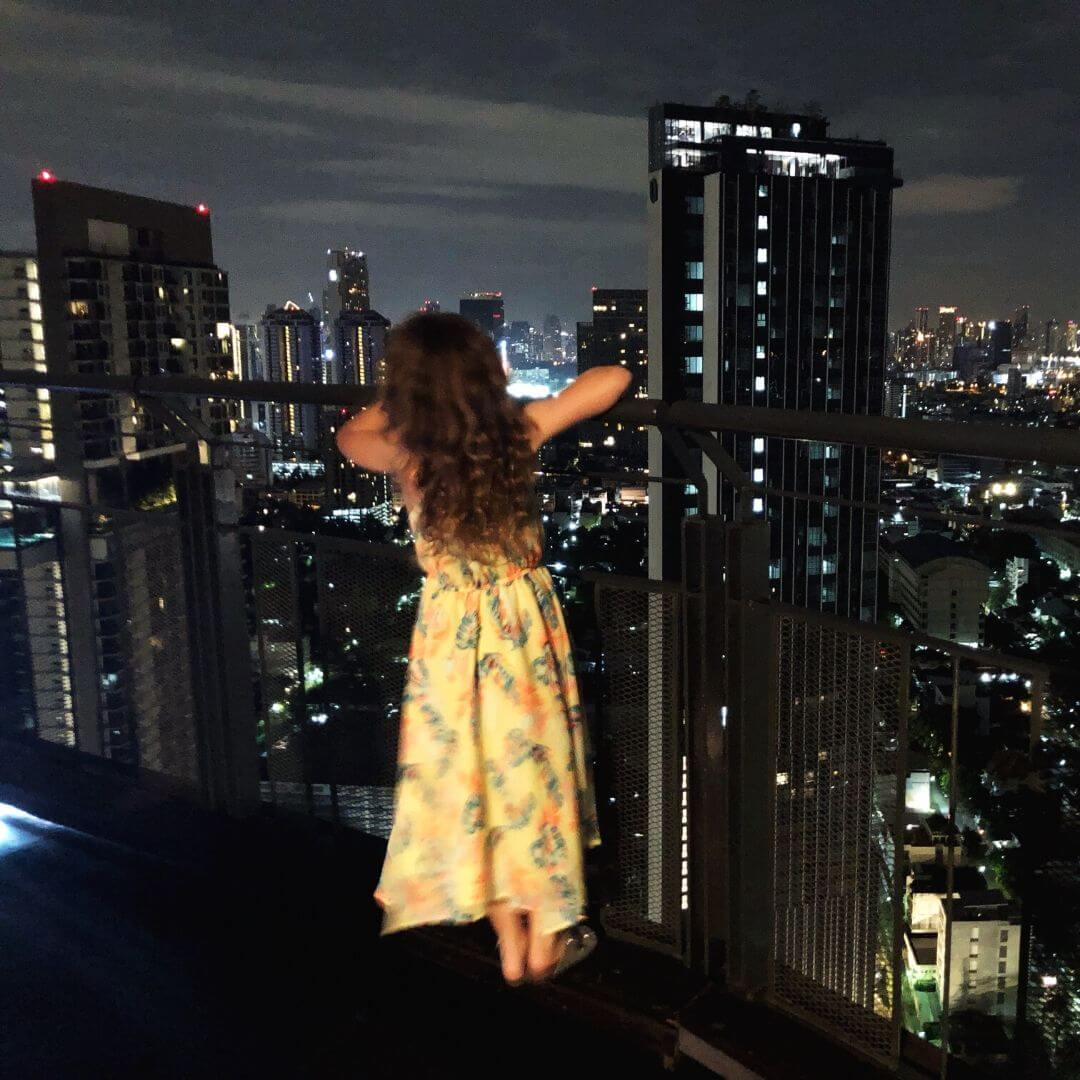 girl in long yellow dress looking out across the bangkok skyline at night