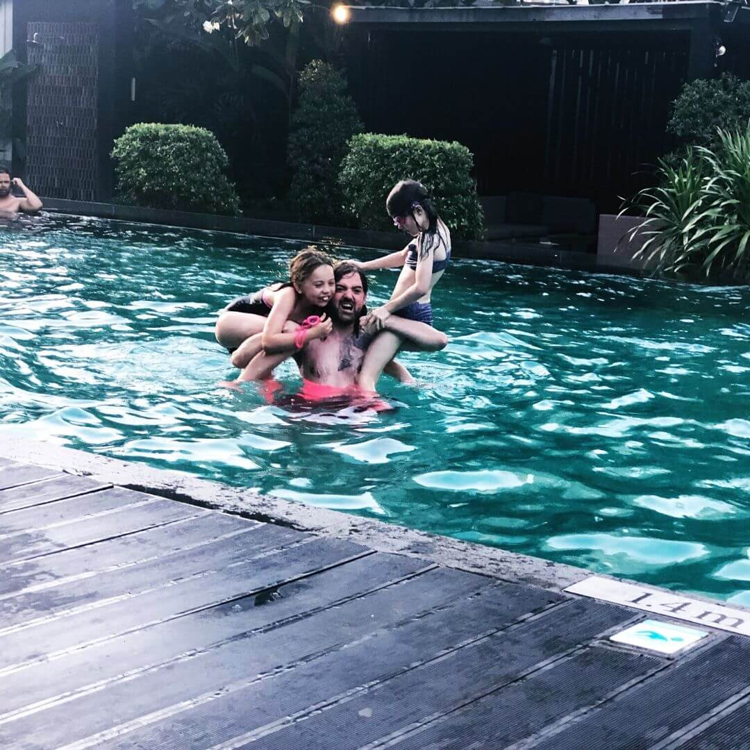 man balancing his daughters on each shoulder in a rooftop pool