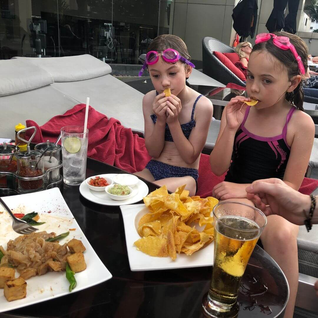 two girls in swimsuits eating beside a pool in bangkok
