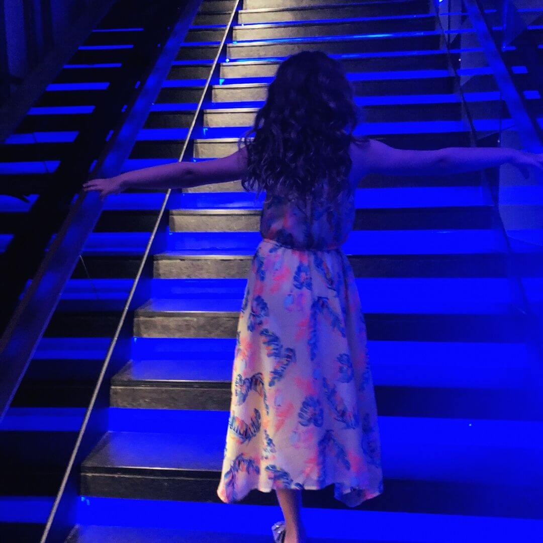 piper quinn walking up the purple lit steps at zoom sky bar
