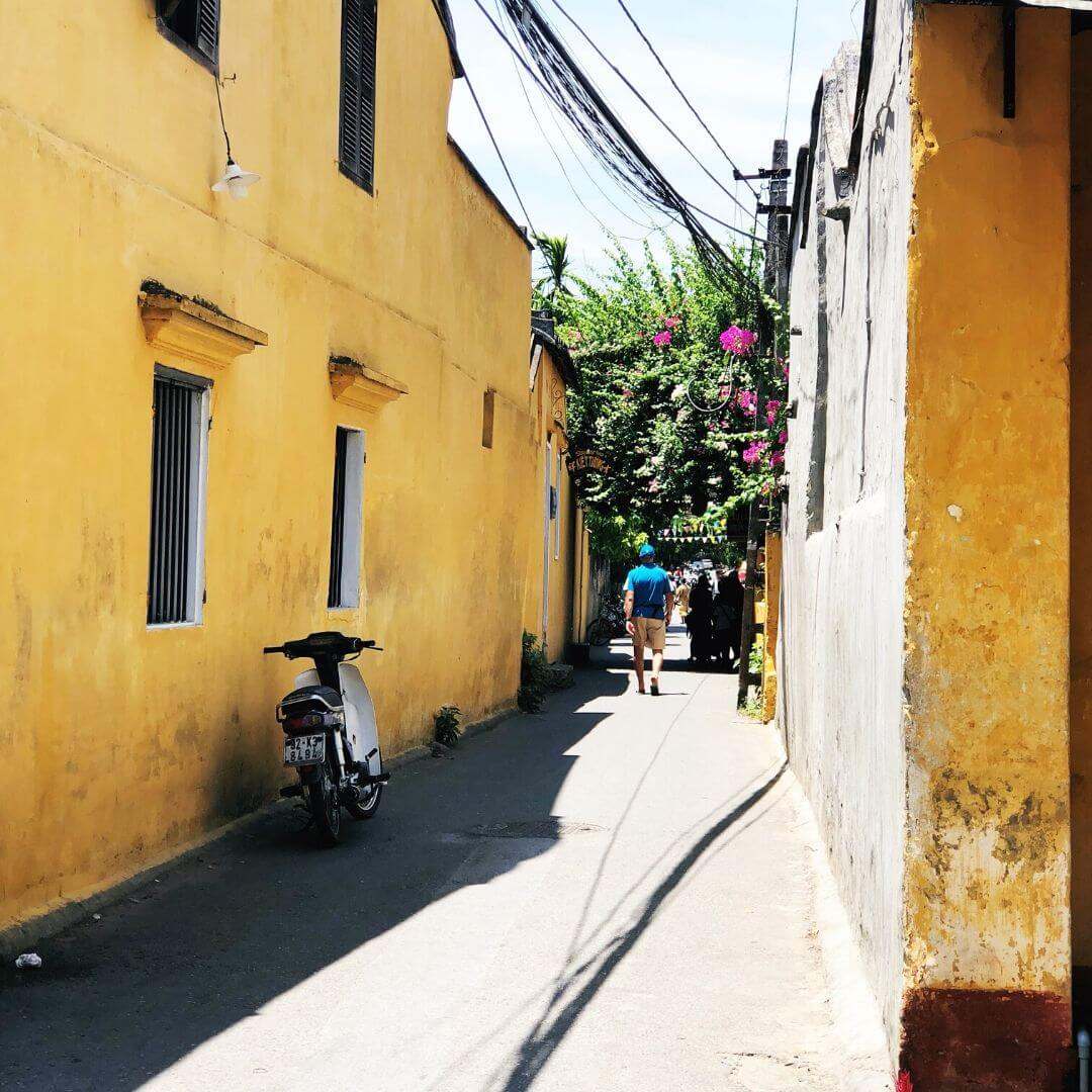 narrow walkway with yellow buildings on each side on a sunny day