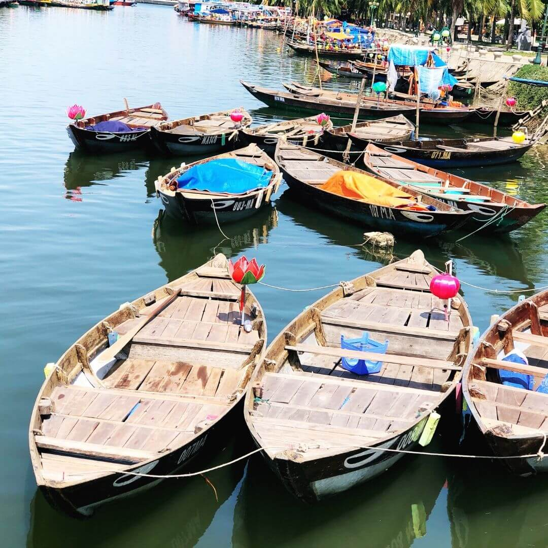 several wooden boats tied up at the side of a river, they have flowers and lanterns on