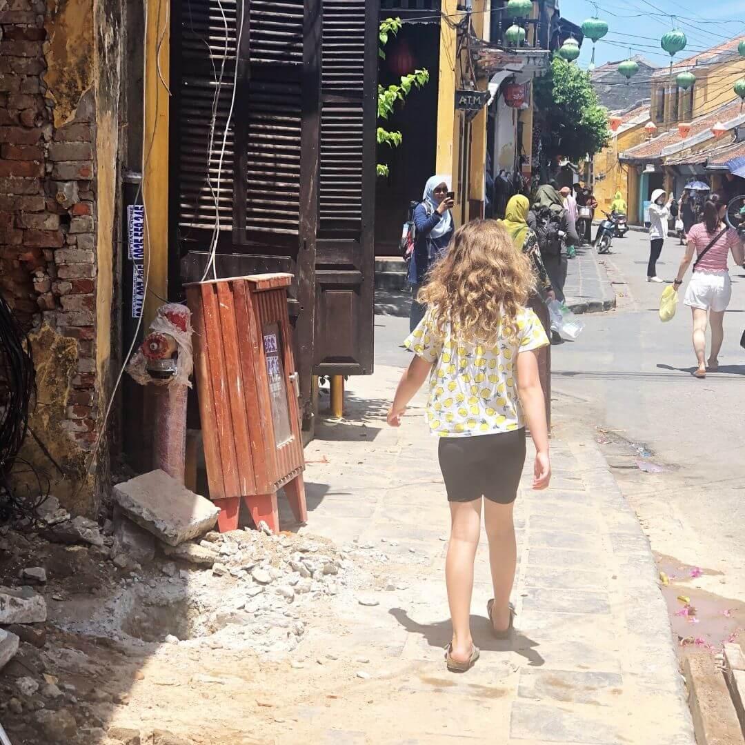 young girl walking along a broken pavement