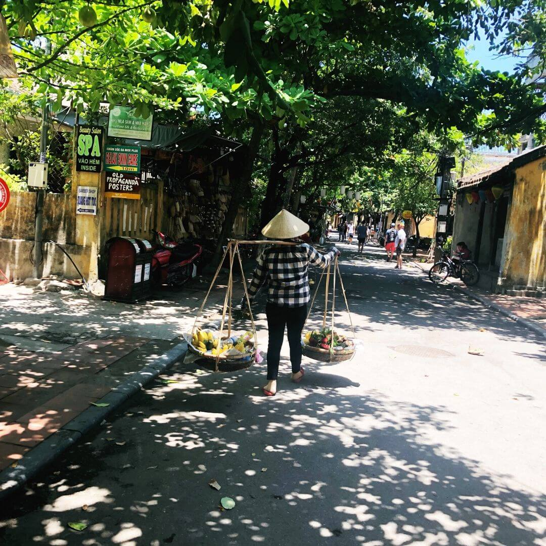 traditional vietnamese lady carrying basket from both shoulders with a pole in between