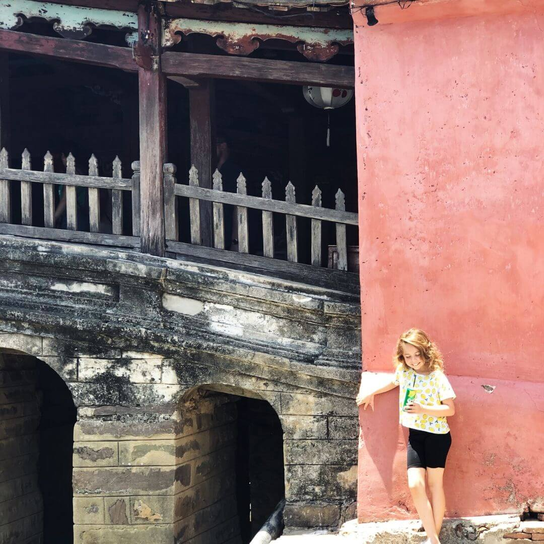 piper quinn drinking a can of sprite outside the japanese bridge in hoi an