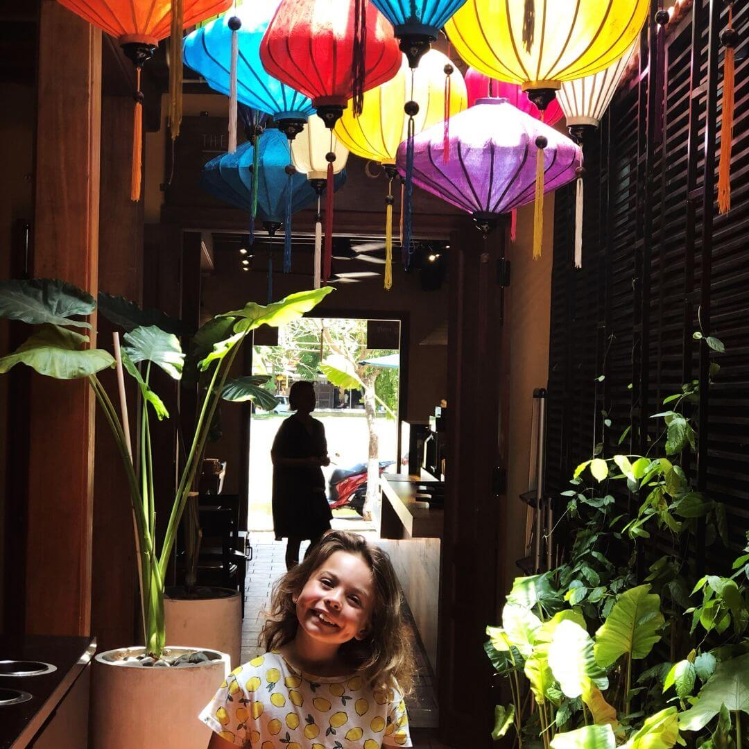 piper quinn in a restaurant in da nang with colourful lanterns hanging over her head