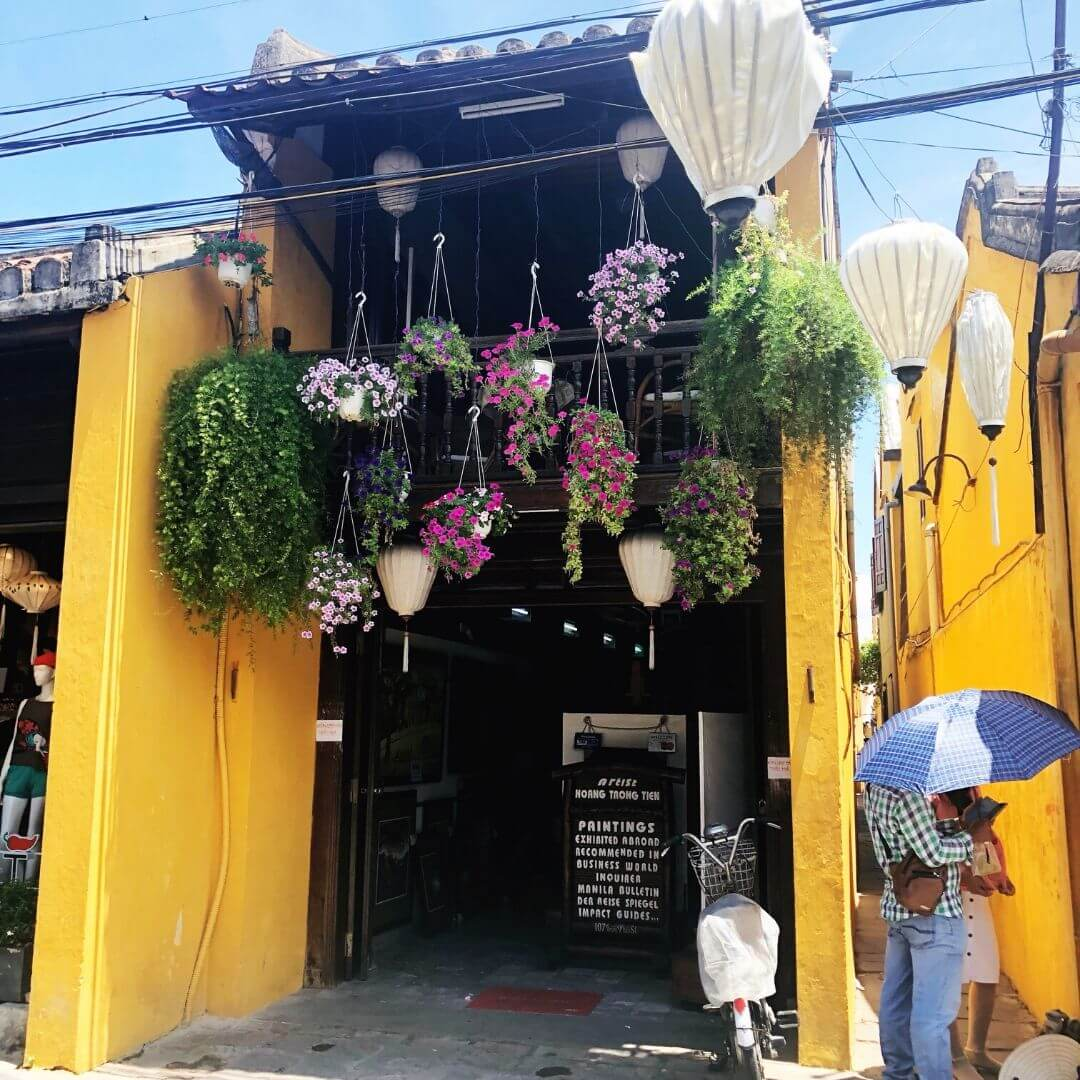 yellow store front with lots of colourful flowers hanging over the doorway