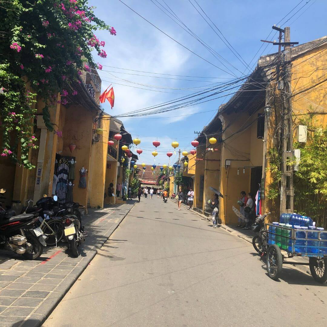 street bordered by yellow buildings and lanterns hanging across in hoi an