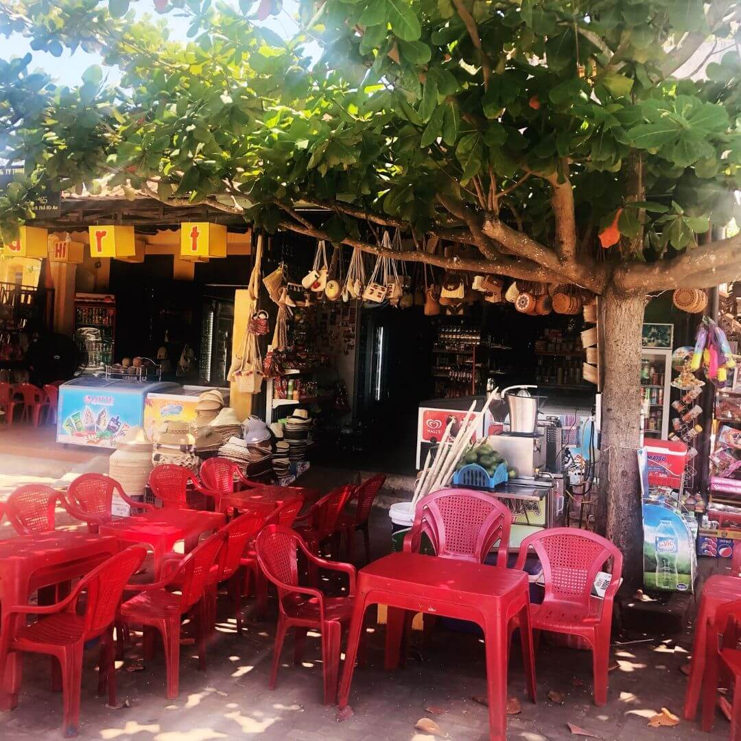 red plastic chairs outside a street cafe in hoi an