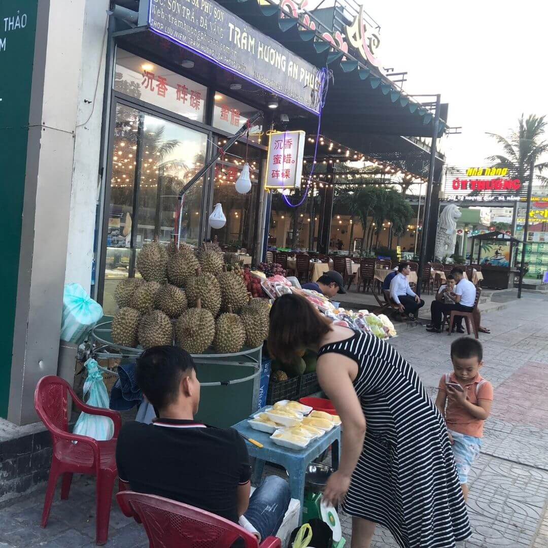 grocery store with a huge pile of durian fruit outside