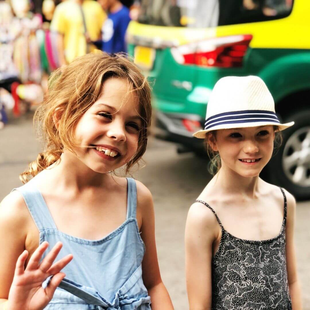 two young girls smiling and waving at the camera